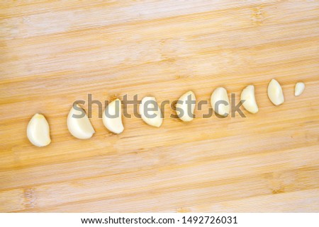 White garlic on timber background. Clean garlic clove size range on wooden cutting board. Peeled garlic ready for cooking. Kitchen table top view. Cookbook or recipe book template. Traditional spice