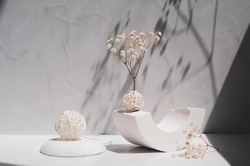 White geometric shape and podium, decorative balls and gypsophila flowers on a gray background. Modern interior still life with sunlight and shadows.