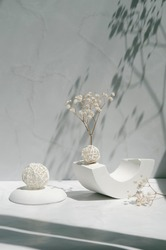 White geometric shape and podium, decorative balls and gypsophila flowers on a gray background. Modern vertical still life with sunlight and shadows in minimalist style.