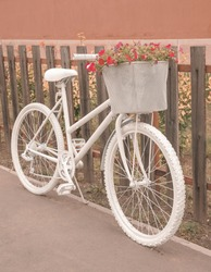 White ghost bike with a basket full of pink flowers parking next to a rustic wooden fence - ghostcycle roadside memorial, reminder to passing motorists to share the road - white bicycle