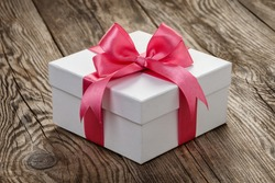 White gift box with a pink ribbon on the old board.