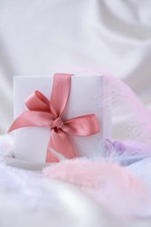 White gift box with pink ribbon on white silk texture background. Colorful bird feather. Holiday concept. Present for Valentines Birthday Mothers Womans day