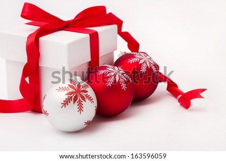 White gift box with red ribbon and christmas balls