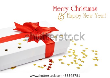 White gift box with red ribbon and golden confetti over white background