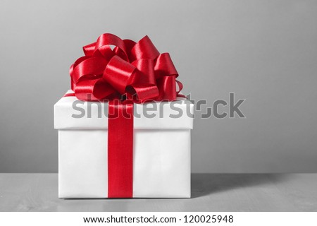 White gift box with red ribbon bow,