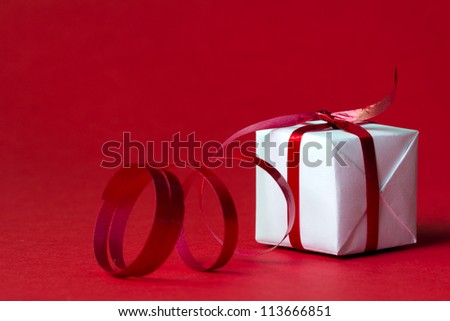 White gift box with red ribbon isolated on red color background