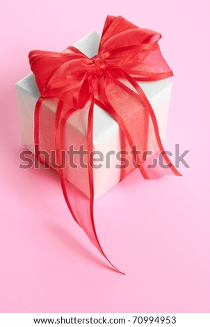 white gift box with red ribbon on pink background
