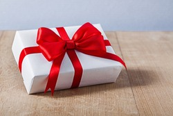 white gift box with red ribbon on wood and blue background