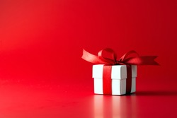 White gift box with ribbon on red background