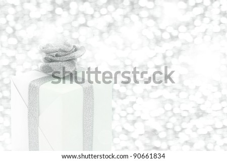 White gift box with silver ribbon's flower on silver background.