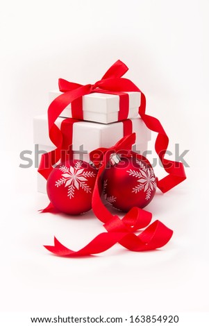 White gift boxes with curly red ribbons and christmas balls
