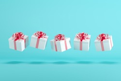 White gift boxs with red ribbon floating on white background. minimal christmas concept idea.