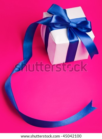white gift in a blue  ribbon on a pink background