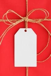 White gift tag mockup on a red christmas gift.