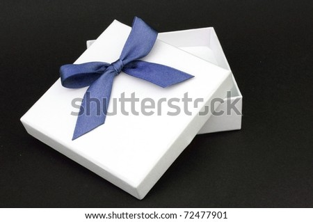 white gift with blue ribbon on black background