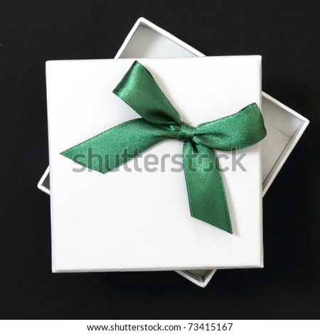 white gift with green ribbon on black background