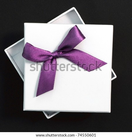 white gift with purple ribbon on black background
