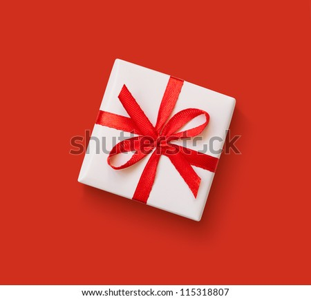 White gift with red ribbon on red background