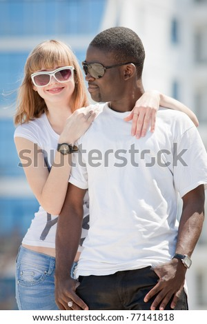 White girl and black guy outdoors. Young man and woman in sunglasses posing