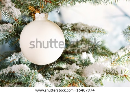 White glass Christmas bauble on a snow encrusted tree