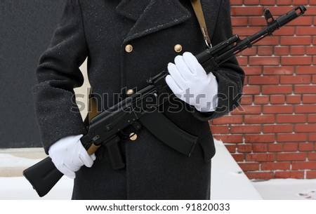 White gloves hands of a honor guard holding a Kalashnikov submachine gun (AK-47)