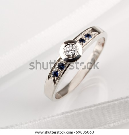 White gold ring whit diamond and sapphire on white satin.
