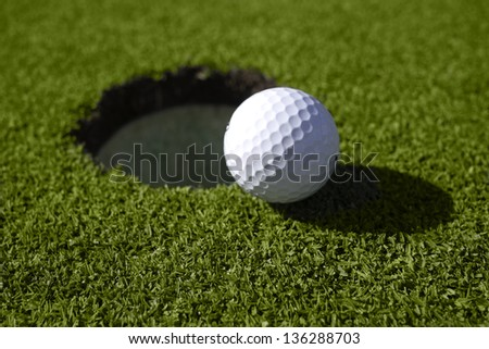 White golf ball lies right at the lip of the golf hole on the green.