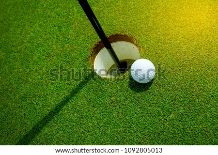 White golf ball near the hole on the green grass at summer - leisure activity