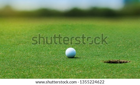 White Golf ball on green course near hole on blurred landscape of golf course in bright day time with copy space. Sport, Recreation, Relax in holiday concept #1355224622