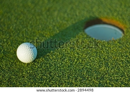 White golf ball on putting green next to hole with long shadow and selective focus on ball