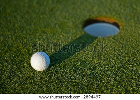 White golf ball on putting green next to hole with long shadow and selective focus on ball - shadow to centre hole.