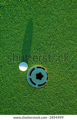 White golf ball on putting green next to hole with long shadow - from top down.