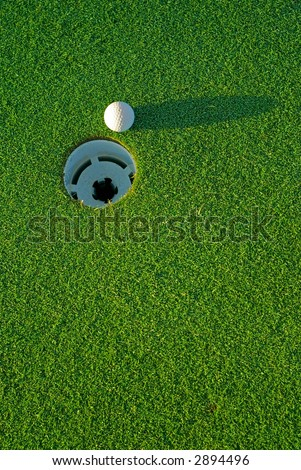 White golf ball on putting green next to hole with long shadow - from top side down.