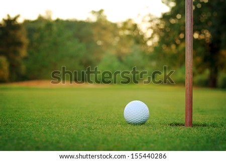 White Golf Ball On Putting Green With Bunker In Background