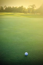 White Golf Ball on the Green Facing the Sunset Vertical