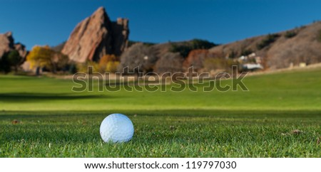 White Golf Ball on the Green With Giant Red Rocks in the Background