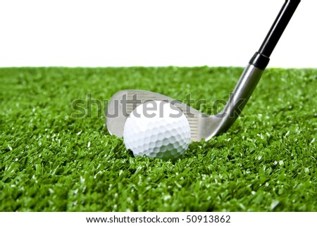 White golf ball with iron(golf club) behind it ready to hit ball on green grass (artificial turf) white background for copy space.