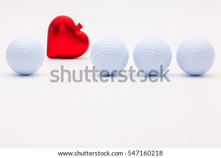 White golf balls and red heart on the white background.