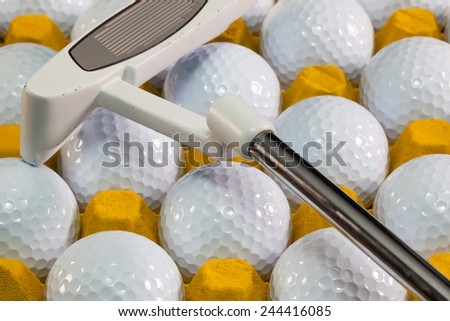 White golf balls in the yellow box and golf equipments