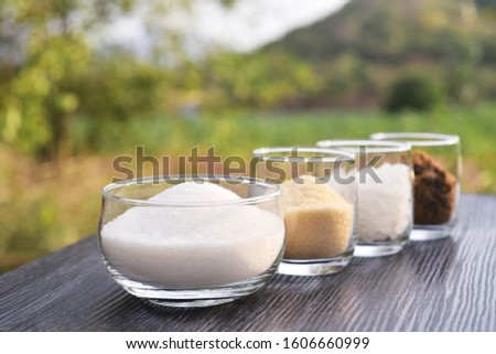 white granulation sugar, raw sugar , crystalline sugar and  brown sugar in roll of clear glasses with natural mountain view background