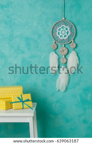 White gray dream catcher , white bedside table , yellow white polka dot boxes in bedroom interior on turquoise textured background. Bedroom decor #639063187