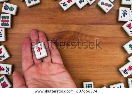 White-green tiles for mahjong on a brown wooden background. Empty place in the center. Red dragon on the hand #607666394