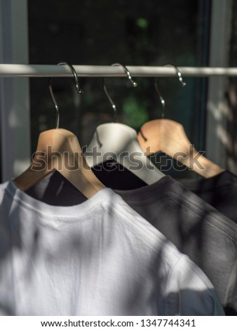White, grey and black t-shirts on hangers, close up view  #1347744341