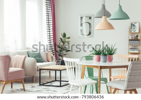 White, grey and green chair at round table under pastel lamps in modern flat interior with sofa and pink armchair #793806436