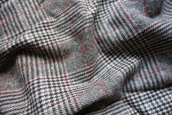 White, grey and red Glen check woolen fabric in soft folds