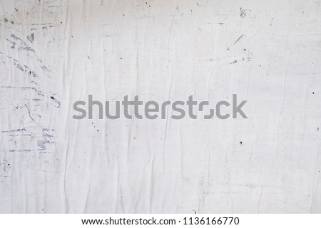 white grey street poster glued to a wall with wheat paste, empty rippled wrinkled creased paper texture