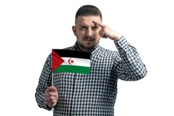 White guy holding a flag of Western Sahara and a finger touches the temple on the head isolated on a white background.
