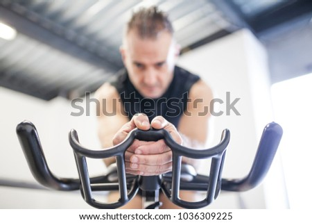 white-haired man in black training indoor cycling in front of window with light holding the handlebar in the middle #1036309225