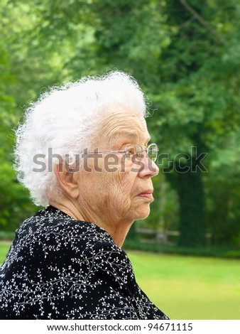 White-haired woman in profile with green trees in background