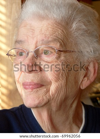 White-haired woman looking out window